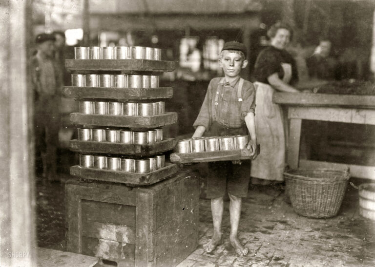 "July 1909. Baltimore, Md. ""One of the small boys in J.S. Farrand Packing Co. and a heavy load. J.W. Magruder, witness."" Photo: Lewis Wickes Hine."