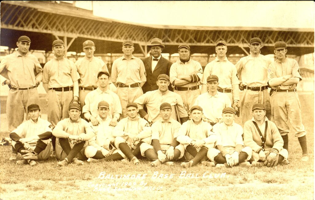 Postcard showing baseball players seated and standing in stadium.