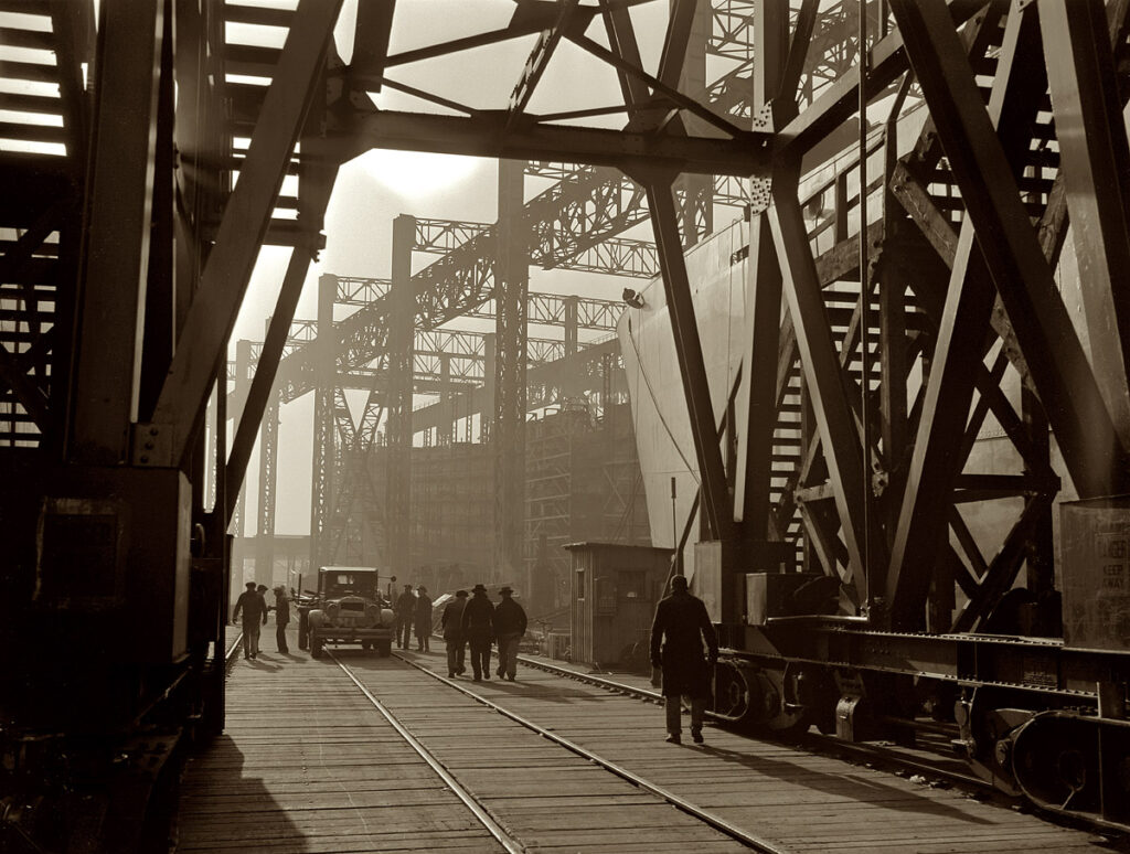 """Bethlehem-Fairfield Shipyards, Baltimore. 1941. """"Between the ways of this large Eastern shipyard run tracks for flatcars carrying materials or sections to be hoisted onto the deck of Liberty ships under construction."""""""