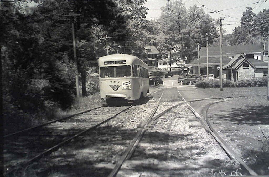 The Catonsville Junction was the terminus for the Baltimore Traction Company's streetcar lines 8, 9, and 14. On this 1950s summer day, a light grey over pencil-yellow Pullman-built PCC (Presidential Car Commission) streetcar departs southbound on the private, quarter mile right-of-way that emptied onto Frederick Road and continued eastward into the city of Baltimore. The little Belgian block gabled structure on the right is still there today, as are the houses in the center rear. The Amoco structure has been replaced by a modern Seven-Eleven convenience store.