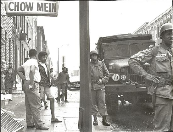 Civilians and National Guard troops standing on the street of Harford Rd. and Lafayette Ave.