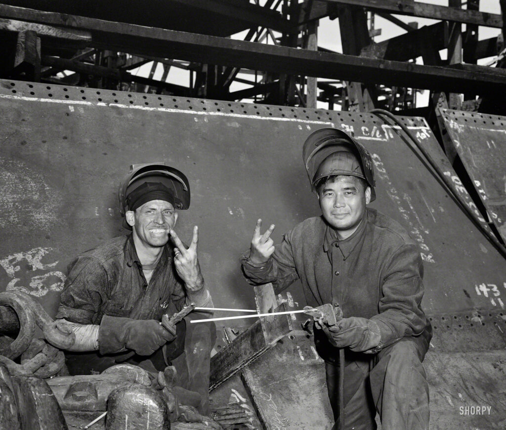 "May 1943. Baltimore, Maryland. ""Electric welders working on the Liberty ship Frederick Douglass at the Bethlehem-Fairfield shipyards."" Photo by Roger Smith for the Office of War Information."