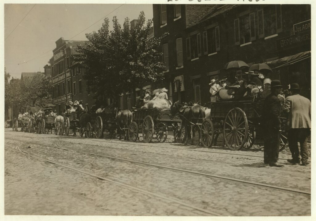 A street full of Baltimore immigrants lined up and ready to start for the country to the berry farms. Wolfe Street, near Canton Avenue, Baltimore, Maryland. Courtesy of Maryland Child Labor Committee. Location: Baltimore, Maryland.