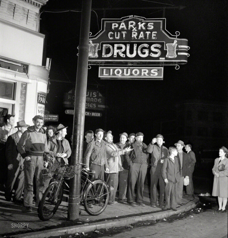 "April 1943. ""Baltimore, Maryland. Third shift workers waiting on a street corner to be picked up by car pools around midnight."" Last seen at the lunch counter. Photo by Marjory Collins for the Office of War Information."