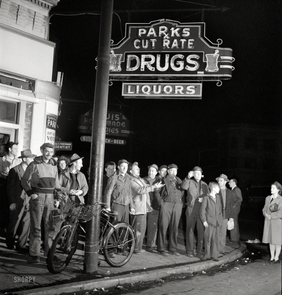 """April 1943. """"Baltimore, Maryland. Third shift workers waiting on a street corner to be picked up by car pools around midnight."""" Last seen at the lunch counter. Photo by Marjory Collins for the Office of War Information."""