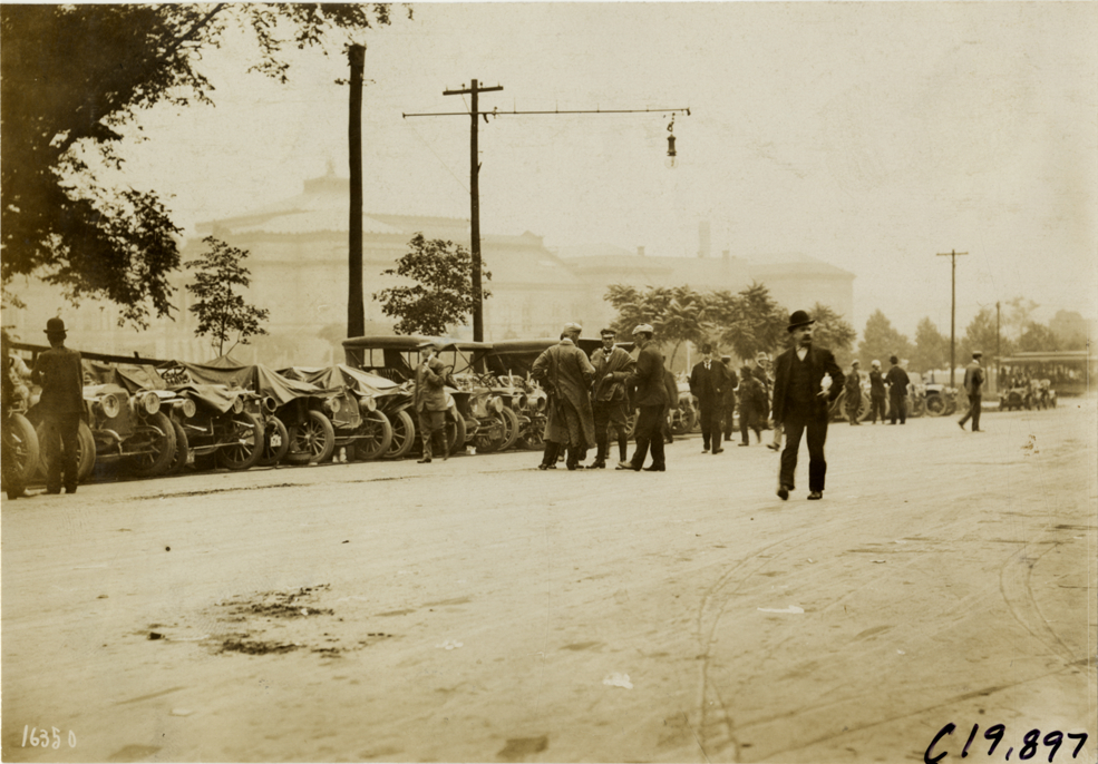 "View of cars lined up in street at Baltimore, Maryland during the 1907 Glidden Tour. Stamped on back: ""Photo by N. Lazarnick, 29 West 42nd Street, New York."" Handwritten on back: ""Cars lined up at Baltimore. Tours--Glidden Tour, 1907."""