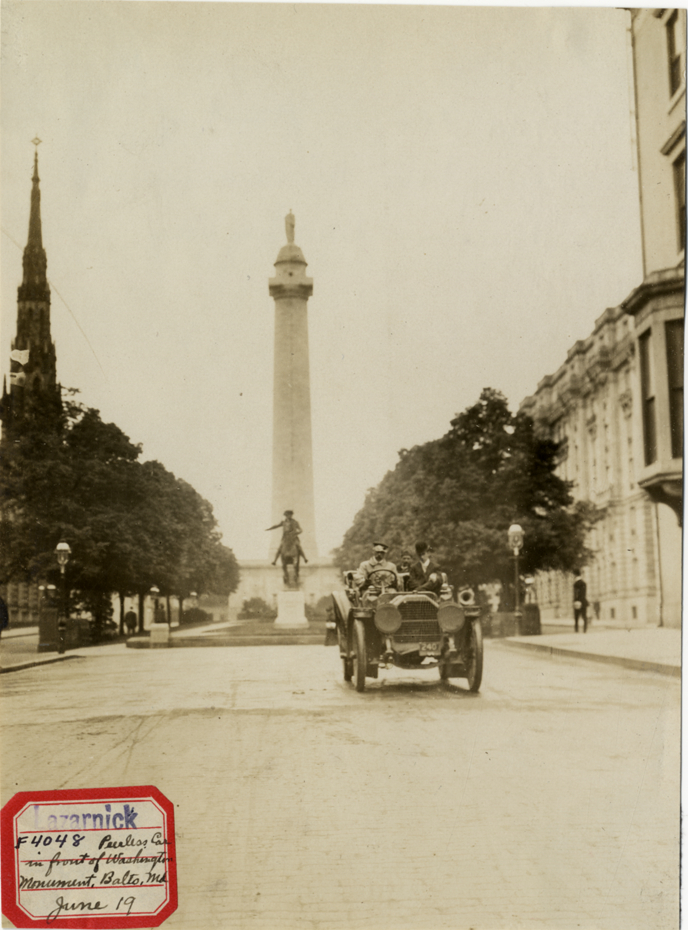 "View of motorists in 1907 Peerless car in front of Washington Monument in Baltimore, Maryland. Label on front: ""Lazarnick. F4048. Peerless car in front of Washington Monument, Balto., Md. June 19."" Stamped on back: ""Photo by N. Lazarnick, 29 West 42nd Street, New York."" Handwritten on back: ""Peerless, 1907. Peerless car in front of Washington Monument, Baltimore. Wednesday, June 19."""