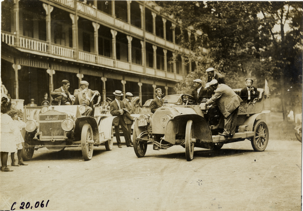 "View of motorists in cars parked in front of inn at Baltimore, Maryland during the 1907 Glidden Tour. Maxwell car on left. Stamped on back: ""Photo by N. Lazarnick, 29 West 42nd Street, New York."" Handwritten on back: ""Tours--Glidden Tour, 1907."""
