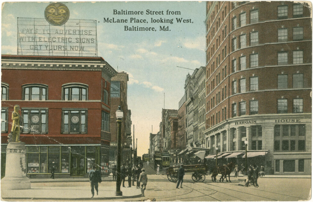 """View of the corner of Baltimore and Liberty Streets. It was named McLane Place for Robert McClane, who was mayor of Baltimore at the time of great 1904 fire, and subsequently committed suicide. The name change did not last, and the location is now the crossing of Baltimore and Liberty Streets again. The monument to the left is that of John Mifflin Hood (1843-1906), a lieutenant in the Confederate Army, later president of Western Maryland Railroad (1874-1902). The sculpture was relocated to Preston Gardens in 1963. The store on the right is Baltimore Bargain House (later American Wholesale Corporation), a firm established by Jacob Epstein (1864-1945). Also in view is an early billboard advertisement boasting, """"Pays to advertise with electric signs. Get yours now."""""""